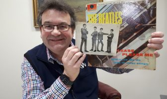 Auctioneer Richard Winterton with the rare autographed photo and a copy of The Beatles' first LP Please Please Me.