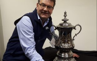 He can dream! Auctioneer Richard Winterton with the replica FA Cup.